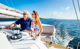 Captain and Passenger at the helm of the Cape Bretoner 1 catamaran sailing on the Bras Do'Or Lake