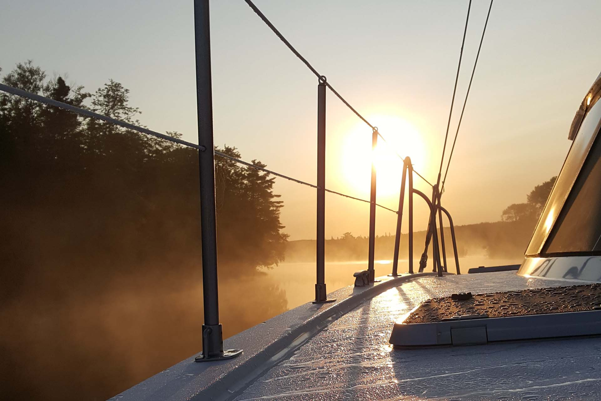 Sunrise through mist on the Bras D'Or Lake as seen from the deck of the Cape Bretoner luxury catamaran